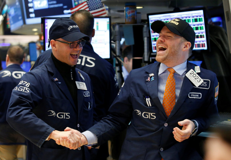 Image: Traders celebrate on the main trading floor of the NYSE as the Dow Jones Industrial Average passes 20,000 after opening of trading session in New York