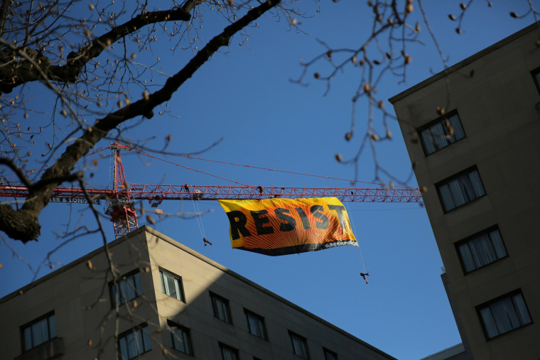 Image: Greenpeace activists hold an anti-Trump protest as they display a banner reading 'Resist' from a construction crane near the White House in downtown Washington