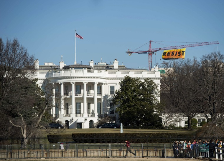 "Image: Greenpeace protesters unfold a banner reading ""Resist"" from atop a construction crane behind the White House on Jan. 25, 2017 in Washington, D.C."