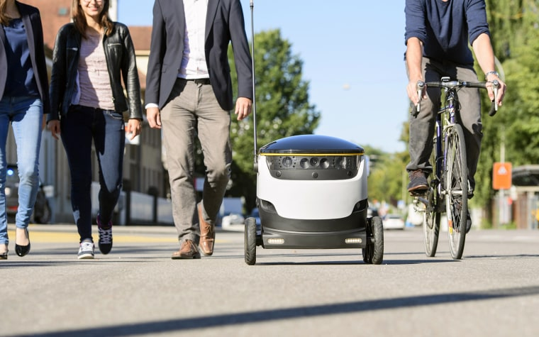 Pedestrians pass a Starship delivery robot.