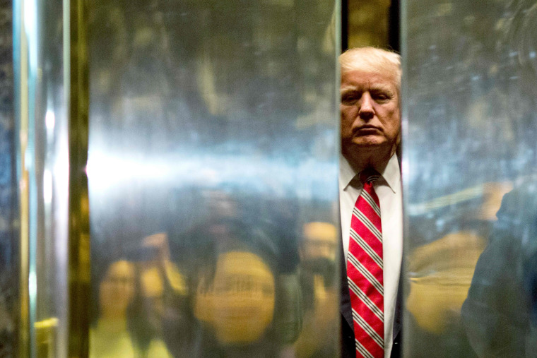 Image: US President-elect Donald Trump boards the elevator after escorting Martin Luther King III