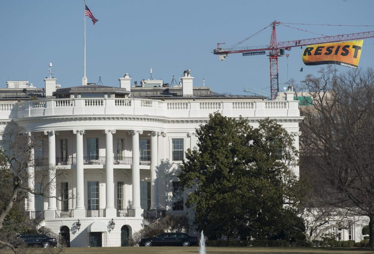"""Image: Greenpeace protesters unfold a \""""Resist\"""" banner from a construction crane near the White House on Wednesday."""