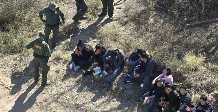 Image: Border Patrol agents watch over immigrants