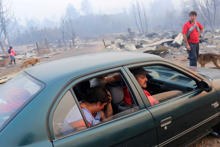 Image: People react while sitting in a car near burnt houses as the worst wildfires in Chile's modern history ravage wide swaths of the country's central-south regions, in Santa Olga