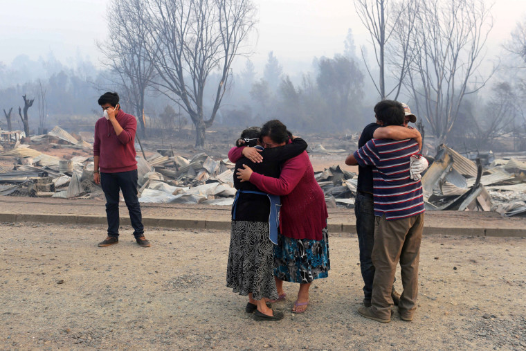 Image: People react while standing next to burnt houses as the worst wildfires in Chile's modern history ravage wide swaths of the country's central-south regions, in Santa Olga