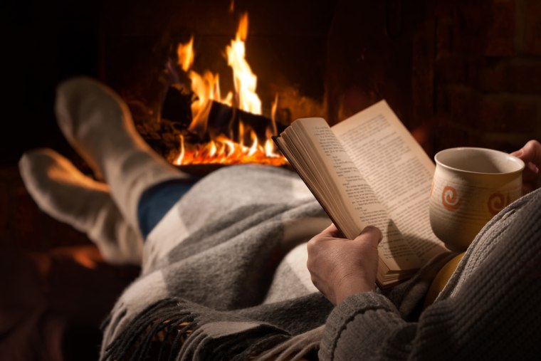 Image: A woman rests with cup of hot drink and book near fireplace.