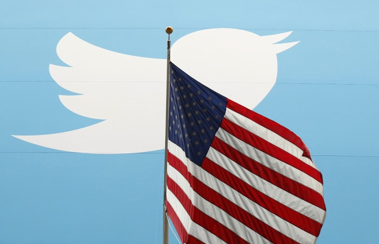 Image: The Twitter logo is shown with the U.S. flag in New York on Nov. 7, 2013.