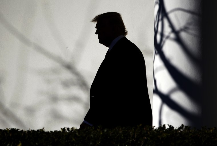 Image: President Donald Trump walks through the Colonnade to the Oval Office after returning to the White House in Washington on Jan. 26.