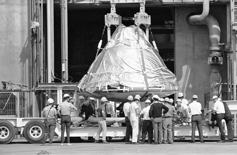 Technicians and officials inspect the aluminum-covered Apollo 1 spacecraft after it was lowered from its booster at Cape Kennedy, Florida on Feb. 17, 1967, so it could be examined to find out what caused the tragedy.