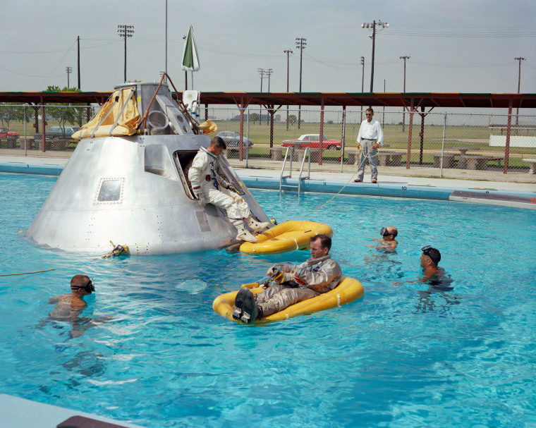 Apollo 1 crew members practice water egress procedures in a swimming pool at Ellington Air Force Base in Houston, Texas. Astronaut Edward H. White II rides on the life raft in the foreground. Roger B. Chaffee sits in the hatch of the boilerplate model of the spacecraft. Virgil I. Grissom waits inside the spacecraft.