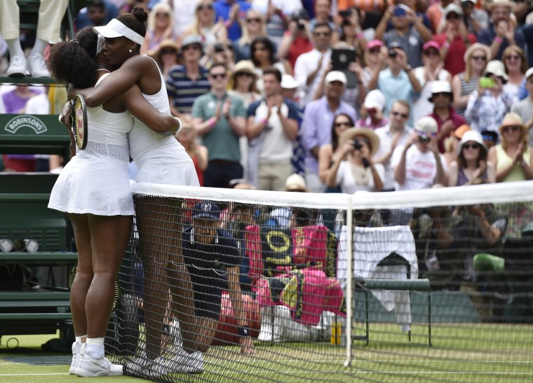 Image: Serena Williams embraces Venus Williams after winning their match at the Wimbledon Tennis Championships in London