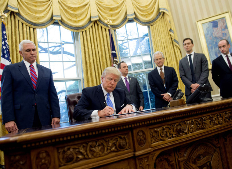 Image: President Donald Trump signs an executive order in the Oval Office of the White House in Washington, D.C., Jan. 23.