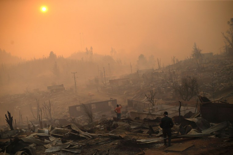 Image: People walk amid the remains of burnt down buildings