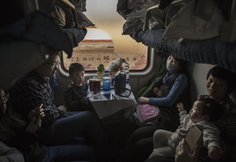 Image: A Chinese family rides on a crowded train between Beijing and Shijiazhuang