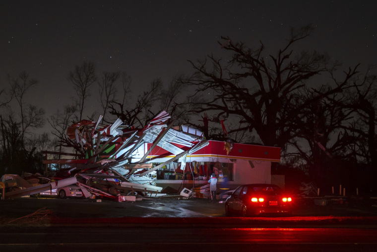 Image: People stop to take a photo of a gas station damaged by an apparent tornado