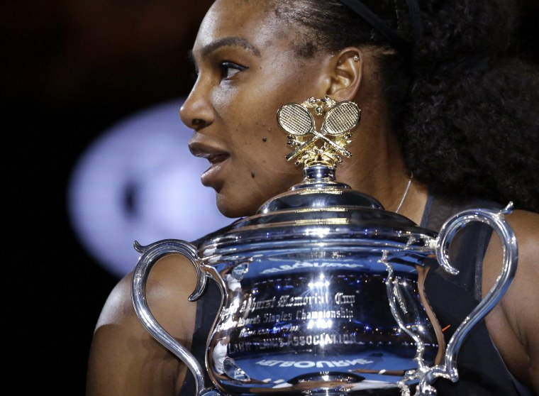 Image: United States' Serena Williams holds her trophy after defeating her sister Venus
