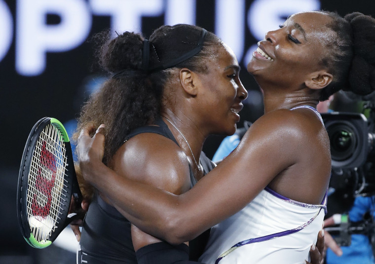 Image: United States' Serena Williams, left, embraces her sister, Venus, as she celebrates after winning the women's singles final at the Australian Open