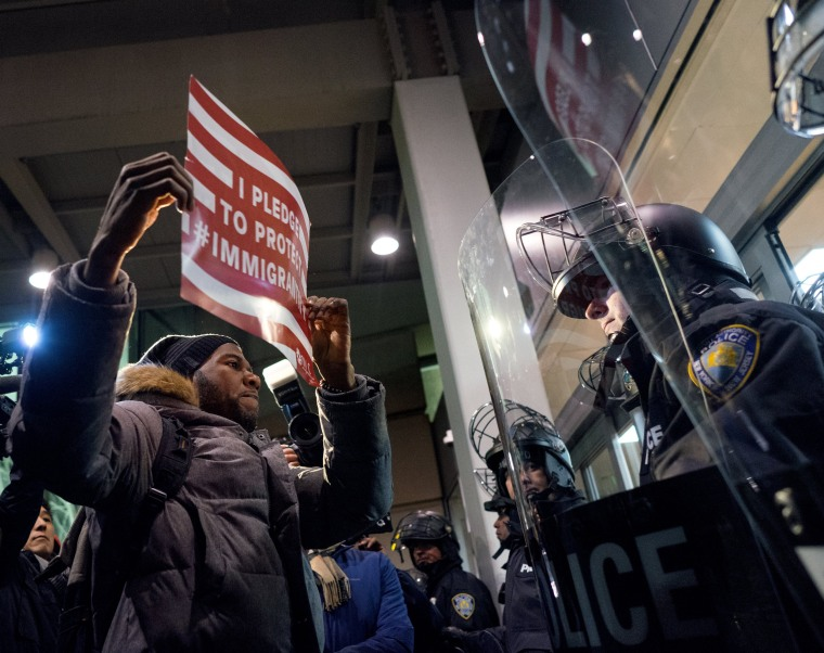 Image: A protester stands facing police officers at an entrance of Terminal 4 at John F. Kennedy International Airport in New York on Jan. 28 after earlier in the day two Iraqi refugees were detained while trying to enter the country.