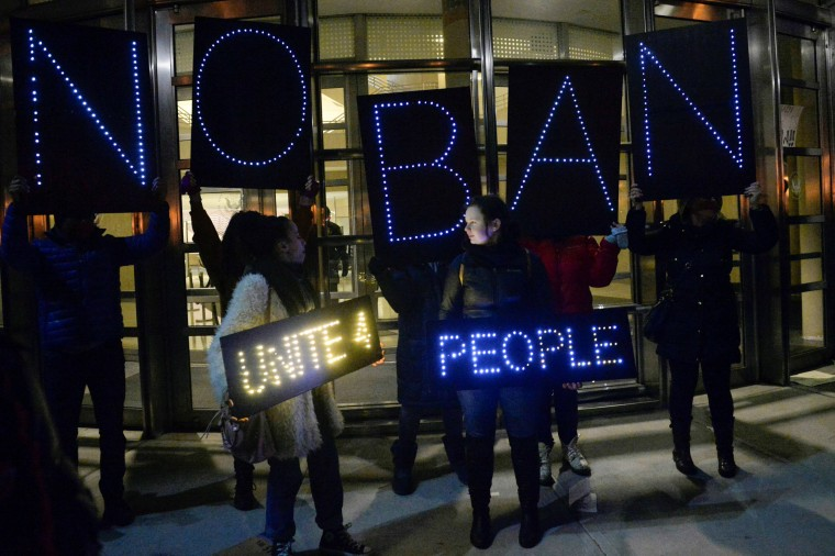 Image: Activists hold placards outside a U.S. Courthouse in Brooklyn, New York