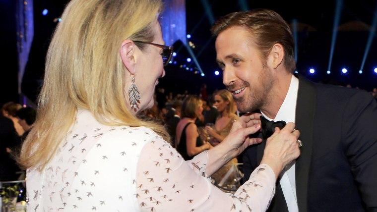 Meryl Streep adjusts actor Ryan Gosling's tie