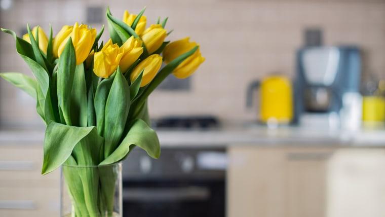 Yellow tulips on kitchen background