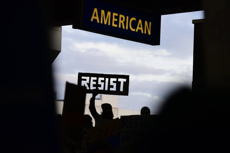 Image: A protester holds up a cutout sign during a protest of President Donald Trump's executive order banning travel