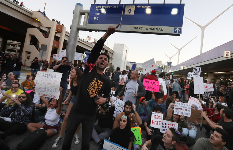Image: Protesters chant as they block a road during a demonstration against the immigration ban imposed