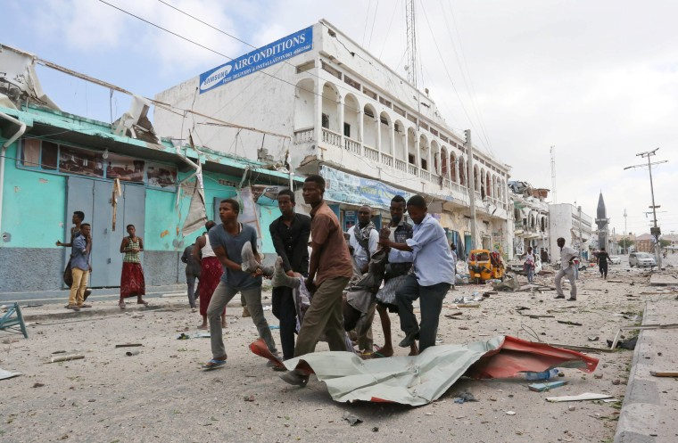Image: Rescuers carry an unidentified injured man from the scene of an explosion in front of Dayah hotel in Somalia's capital Mogadishu