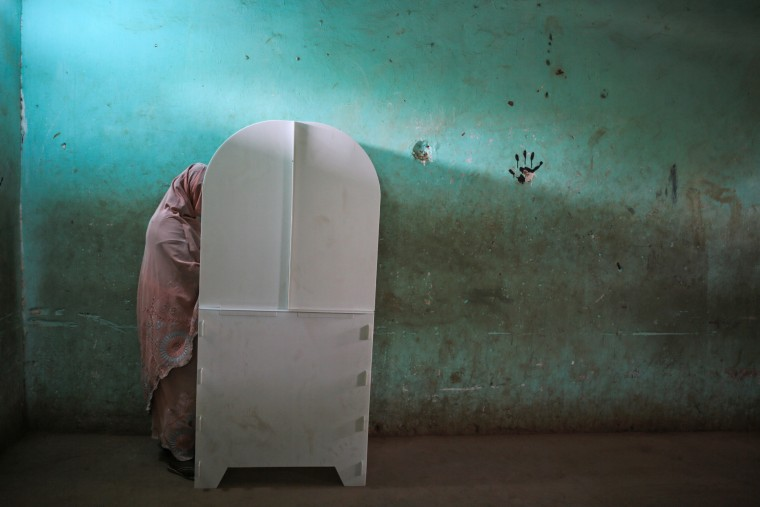 A Sudanese woman fills her ballot at a polling station on the first day of Sudan's presidential and legislative elections, in Izba, an impoverished neighborhood on the outskirts of Khartoum, Sudan, on April 13, 2015.