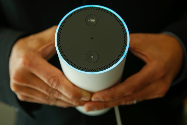 Image: An attendee holds an Echo device during the U.K. launch event for the Amazon device on Sept. 14.