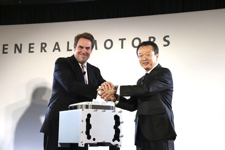 Mark Reuss, GM Global Product Development Chief, and Toshiaki Nikishiba, President and CEO of Honda North America, shake hands by a fuel-cell stack.