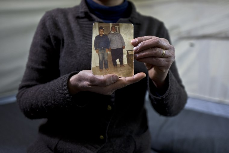 Image:  In this Jan. 18, 2017 photo, Habeeba Waqas, 40, a Syrian refugee from Aleppo, holds a photograph showing her husband Mohammed and her father in law Suliman.