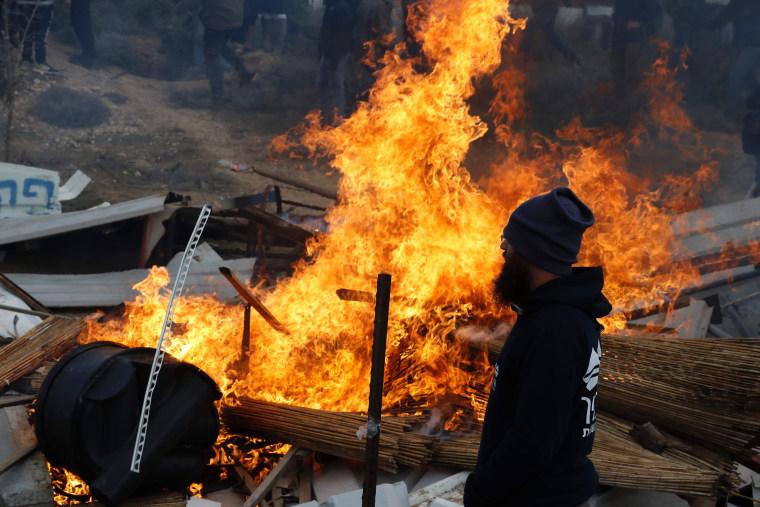 Image: An Israeli settler stands next to burning furniture