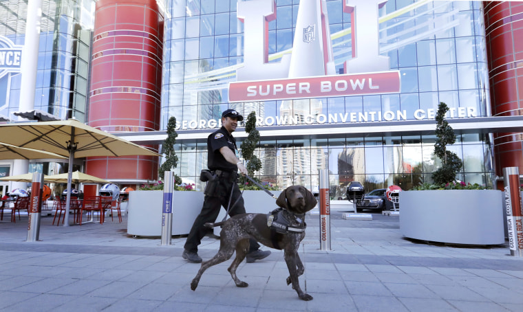 Image: Officer Keith McCart, of the Long Beach, Calif. Police Department, patrols with K-9 Pidura outside the George R. Brown Convention Center, the NFL Super Bowl 51 football media center and site of the NFL Experience, Jan. 31, 2017, in Houston.