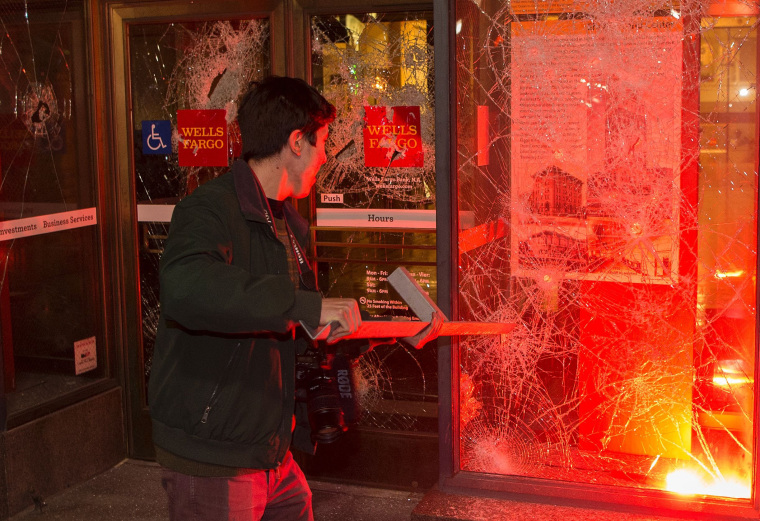 Image: A man pulls a piece of metal out of a window as a flare burns inside a Wells Fargo Bank