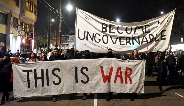 Image: Protesters march with signs in Berkeley