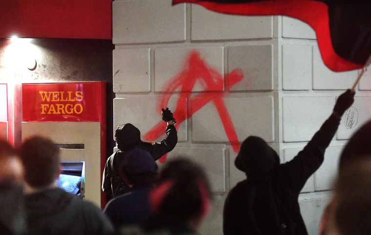 Image: A rioter paints an anarchy symbol on a Wells Fargo bank