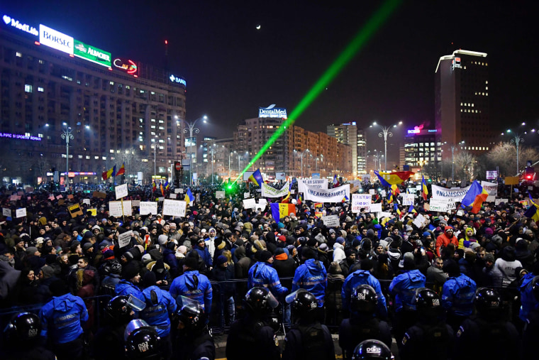 Image: Romanian riot police stand guard as people demonstrate against controversial decrees to pardon corrupt politicians and decriminalize other offenses in front of the government headquarters in Bucharest, on Feb.1, 2017