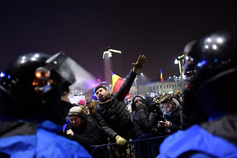 Image: Romanian riot police stand guard as people demonstrate against controversial decrees to pardon corrupt politicians and decriminalize other offenses in front of the government headquarters in Bucharest, on Feb. 1, 2017.