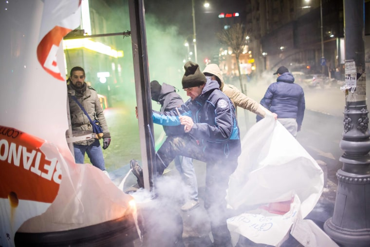 Image:Protesters destroy outdoor advertisment during a protest in front of the government headquarters  against controversial decrees to pardon corrupt politicians and decriminalize other offenses in Bucharest on Feb. 1, 2017.