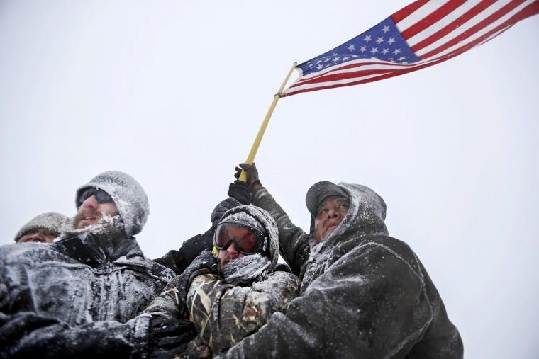 Image: Military veterans huddle together to hold a United States flag against strong winds during a march to a closed bridge outside the Oceti Sakowin camp where people have gathered to protest the Dakota Access oil pipeline in Cannon Ball, N.D., Dec. 5,