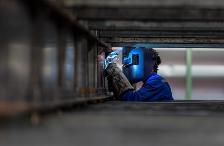 Image: A factory worker wears a protective mask.