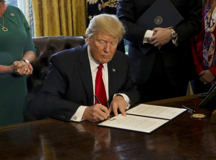Image: U.S. President Donald Trump signs Executive Orders in the Oval Office of the White House, including an order to review the Dodd-Frank Wall Street to roll back financial regulations of the Obama era Feb. 3, 2017.