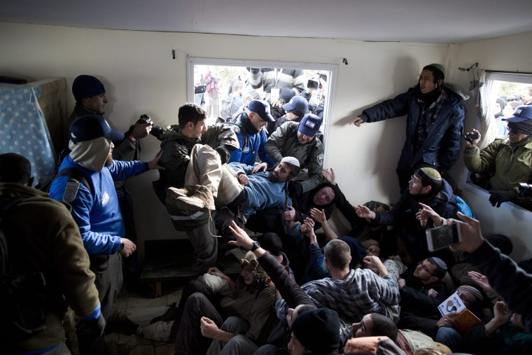 Image: Israeli security forces try to arrest settlers who hold each other in a house during the evacuation of the illegal Jewish settlement of Amona, in the West Bank, on Feb. 1.