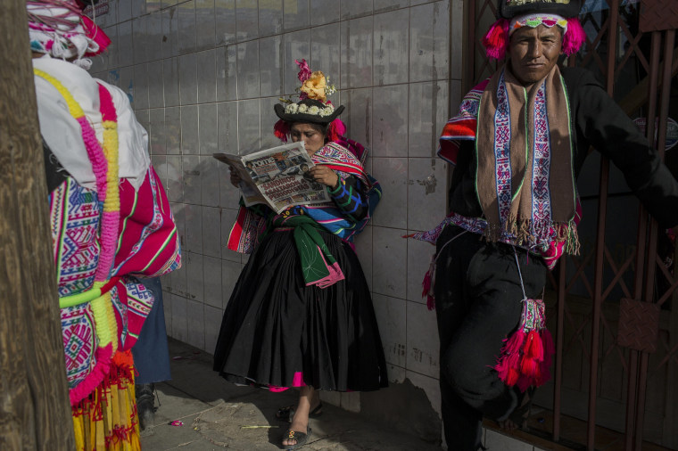 Image: A dancer reads a newspaper while waiting to perform during Virgin of Candelaria celebrations in Puno, Peru on Jan. 29.