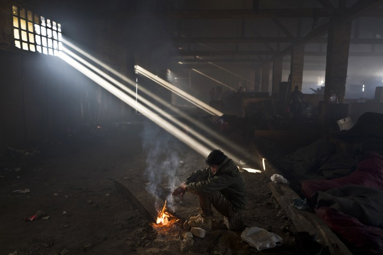 Image: An Afghan refugee warms himself by a fire in an abandoned warehouse in Belgrade, Serbia on Jan. 30.
