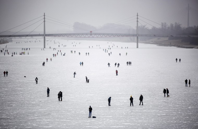 Image: People walk and skate on the frozen New Danube discharge channel in Vienna, Austria on Jan. 29.