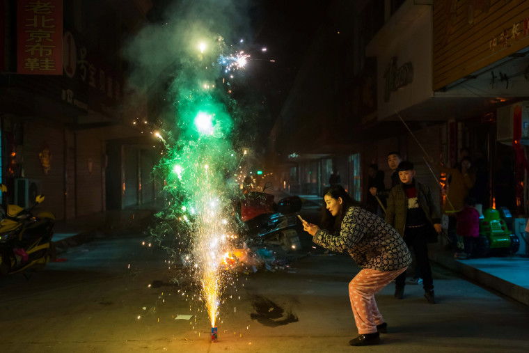 Image: A woman takes pictures of firework on the eve of the Chinese Lunar New Year, or the Spring Festival, in Lianyungang, Jiangsu province, China on Jan. 27.