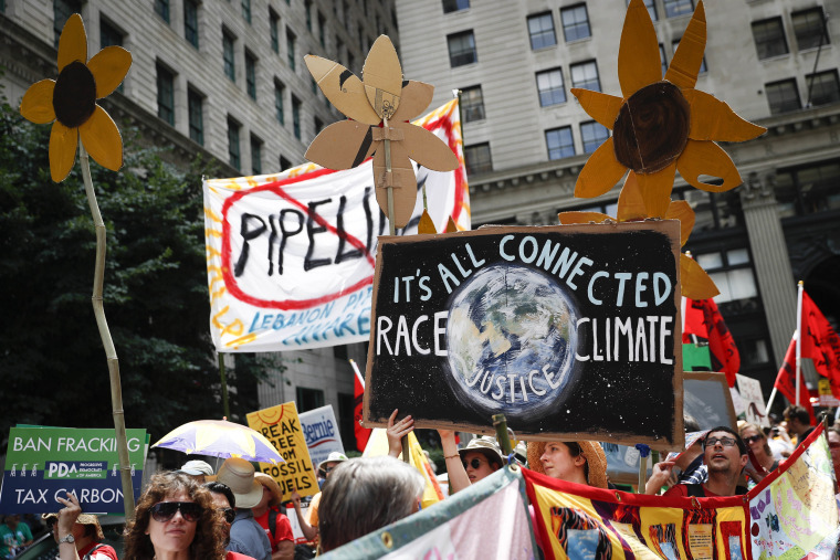 Image: Climate change activists carry signs as they march during a protest in downtown in Philadelphia a day before the start of the Democratic National Convention on July 24, 2016.