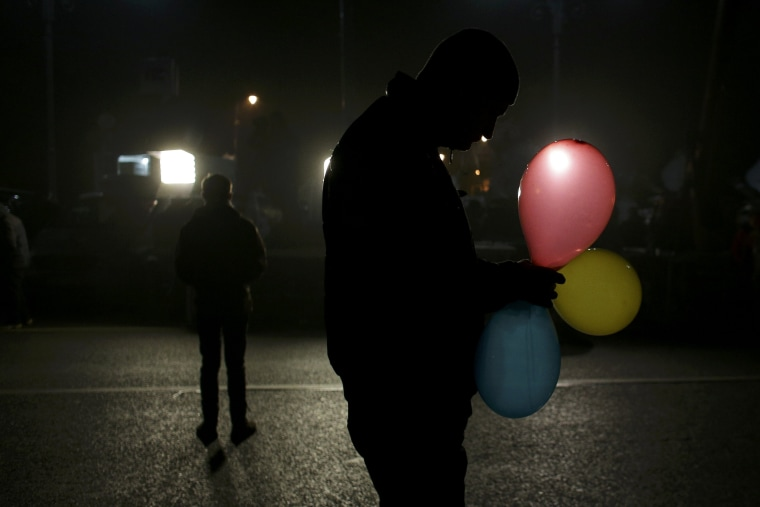 Image: A man holds balloons in the colors of the Romanian flag.
